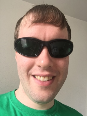 Selfie of me wearing green-tinted sunglasses and smiling.