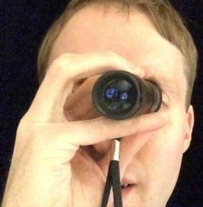 Image shows me holding my monocular - a small telescope - up to my eye