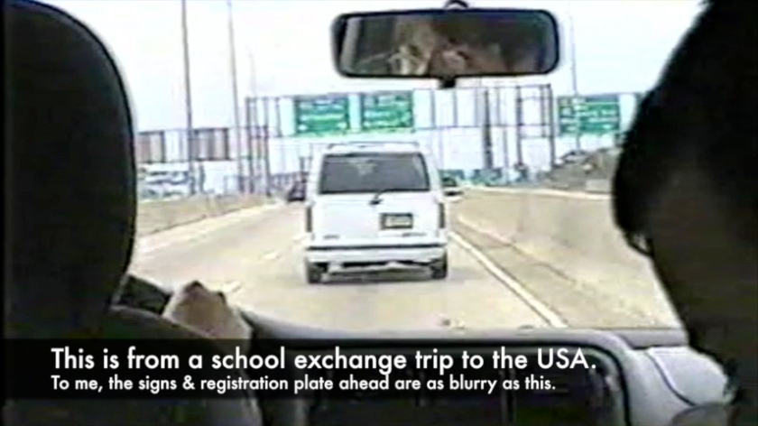 Camcorder video screenshot, taken inside a car on a motorway in America, showing blurry signs and number plate ahead of us. Caption reads - This is from a school exchange trip to the USA. To me, the signs and registration plate ahead are as blurry as this.