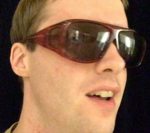 Image shows me wearing my sunglasses, which have small anti-glare glass panels on the arms, and above and below the eyes, in addition to the central lenses themselves