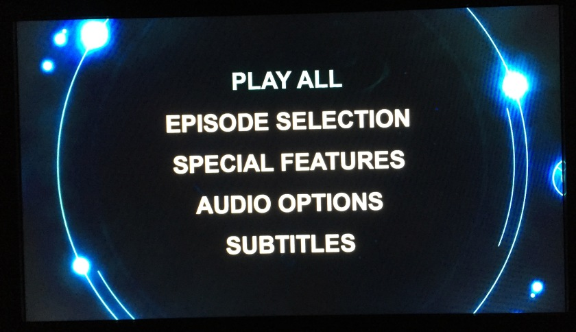 Doctor Who DVD Audio Menu Screen - Main Menu, showing Play All, Episode Selection, Special Features, Audio Options and Subtitles, all in large clear print. Background behind text is black - circular shapes and lights adorn the edges.
