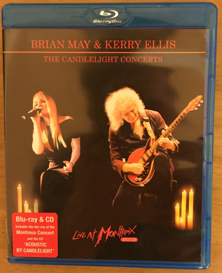 Blu-Ray cover for Kerry Ellis & Brian May's Candlelight Concert, showing Kerry singing and Brian on guitar, with candles behind them. Set includes Montreux Concert Blu-Ray and Acoustic By Candlelight CD.