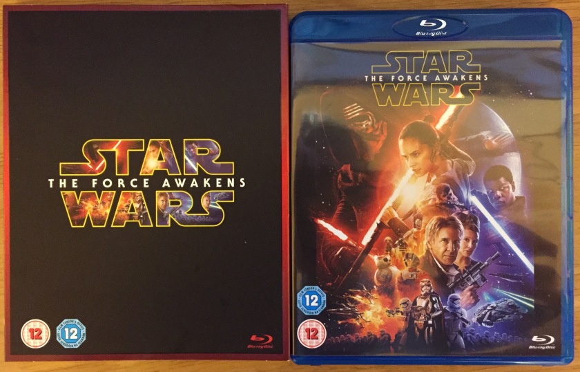 Star Wars Blu-Ray. Outer slipcase is black with Star Wars logo, the large lettering containing images of the main characters. Inner blu-ray case shows a montage of characters, lightsabers and spaceships.