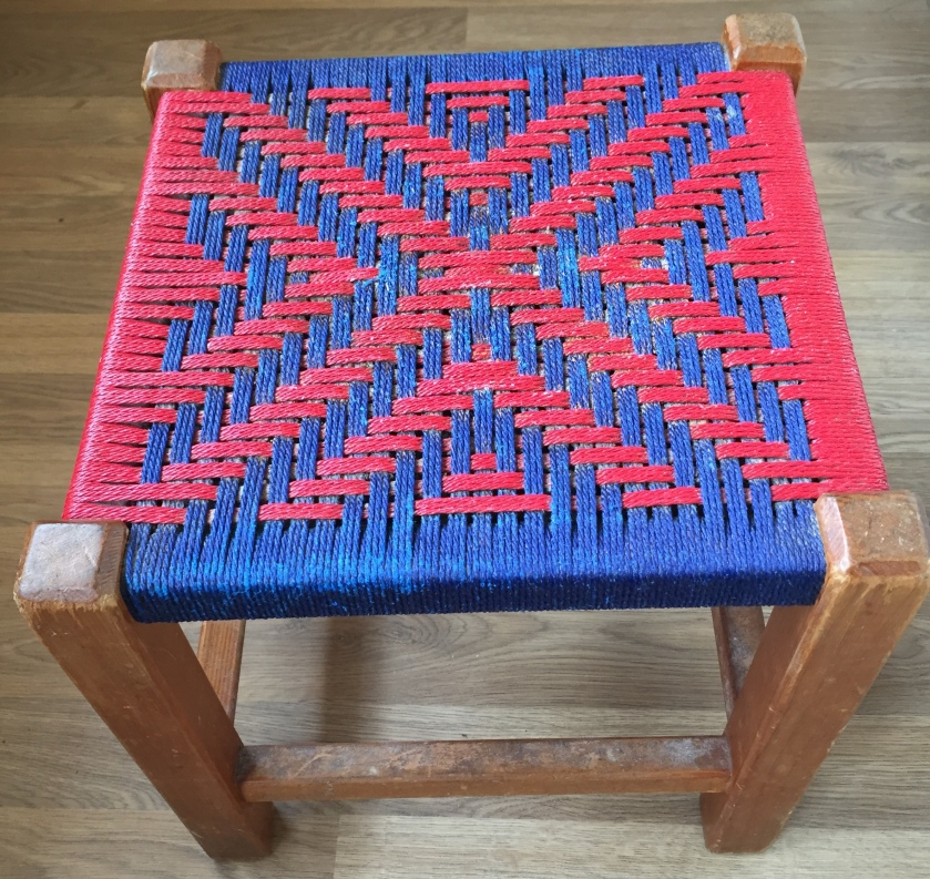 Small, square, flat stool with wooden legs. Seat has alternating blue and red pattern. From each edge, triangular arrow shapes of alternating colour and increasing size work towards the centre, which is a red X shape joining all the corners.