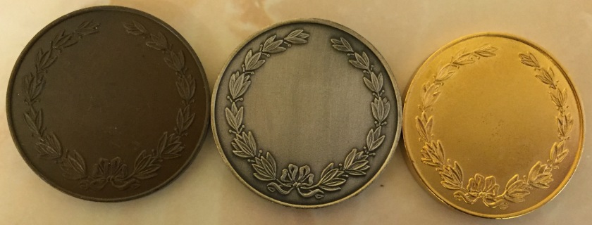 Bronze, silver and gold Ten Tors Medals. The backs have a decorative leafy border going around the edge, while the centre of the medal is plain.