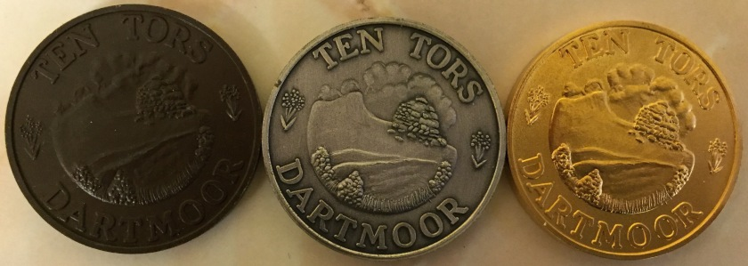Bronze, silver and gold medals, saying Ten Tors at the top and Dartmoor at the bottom. Embossed centre has a few small trees at the bottom, with two small hills behind it. A much bigger hill is behind that, with a big pile of rocks, all under a cloudy sky.