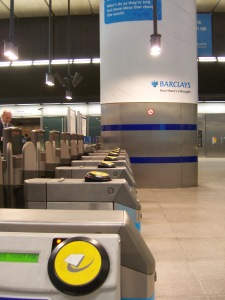 London Underground ticket barriers, with the big round yellow pads for tapping an Oyster Card.