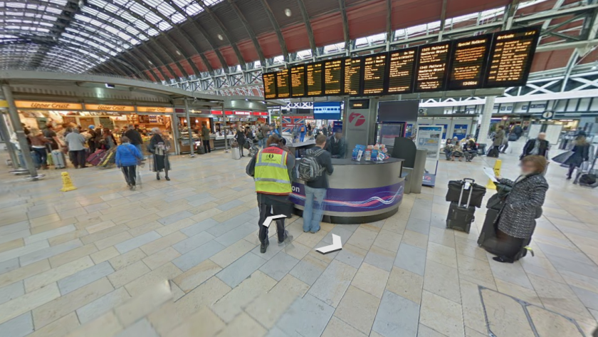 Google Street View image of Paddington train station. Shows information desk with departure boards behind, and food outlets to the side, plus passengers and staff in the area.