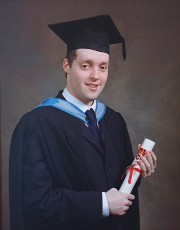 My graduation photo. I'm wearing a dark navy suit and tie, with light blue strap around the neck, and a mortar board on my head. I'm smiling while holding a rolled up certificate tied with a red ribbon.
