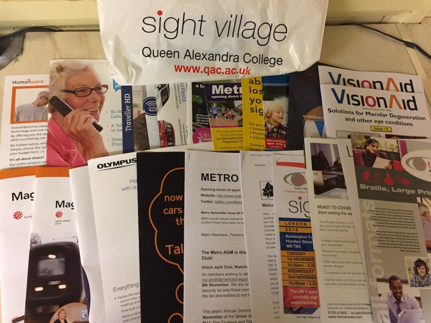 Large collection of booklets and leaflets from Sight Village for various organisations. At the back is a bag that says Sight Village, Queen Alexandra College, www.qac.ac.uk.