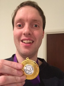 Me wearing my Thinking Bob medal. Gold surrounds a white circle in the center, which contains the text