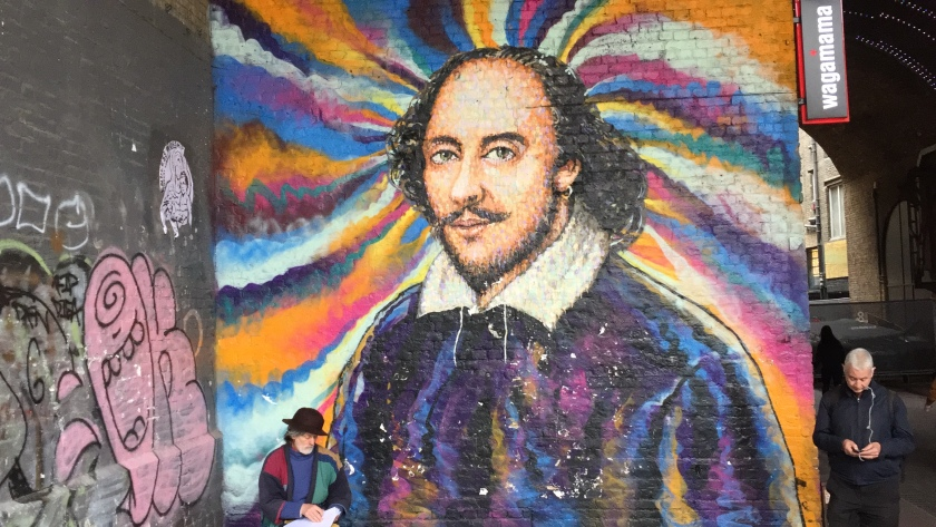 A large wall-sized painting of William Shakespeare, with a colourful swirly background. The artist is next to it at the bottom, still working on it.