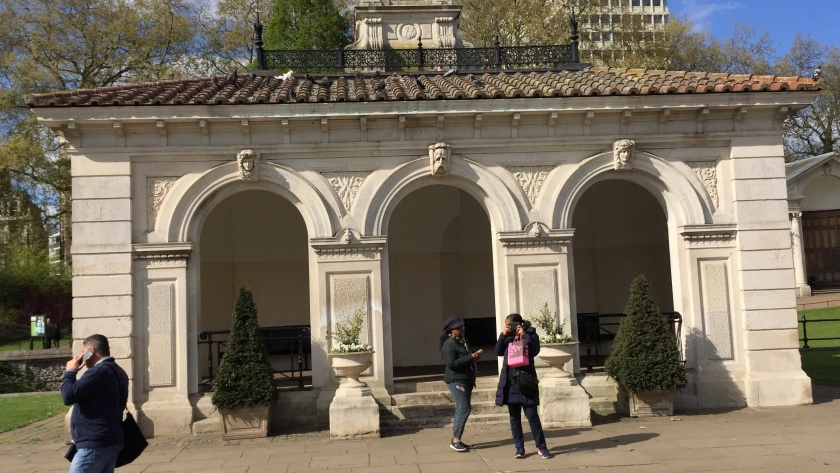 The side of a building in the Italian Gardens, with 3 large arches, each with a figure of a head at the top of them.
