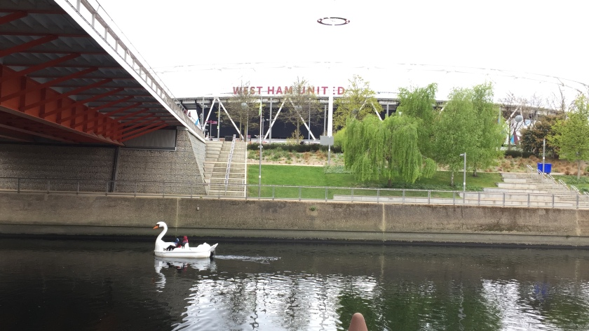 A swan pedalo carrying two riders moves along the river and under a bridge, while the West Ham Stadium looms in the background, partially obscured by some small trees.