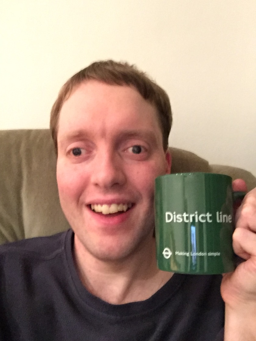 Me holding a green mug, which has District Line in big white letters in the centre. Below that, in smaller white print, is the London Transport roundel logo, with the words Making London Simple.