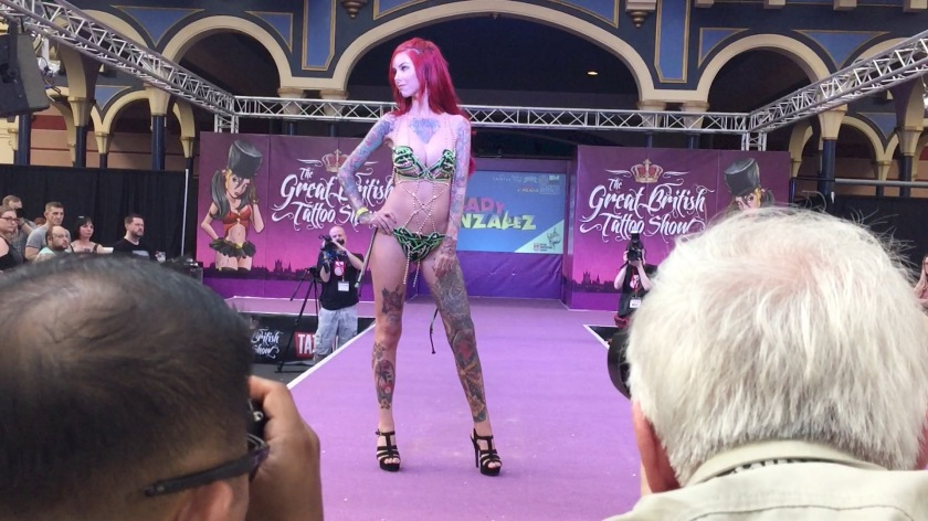 Red-haired tattooed lady modelling lingerie on the catwalk stage.