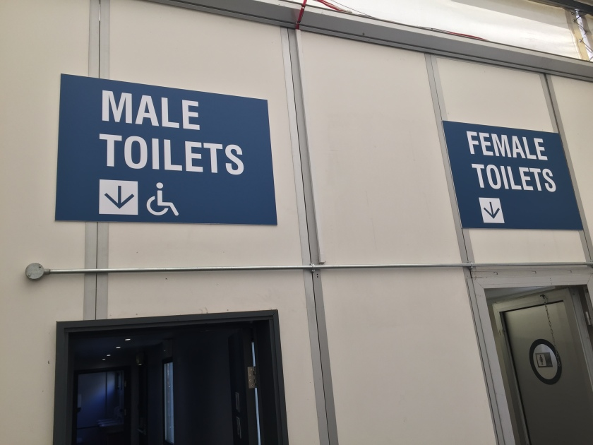 Signs above the toilet doors at Alexandra Palace, with very large white text on a dark blue background.