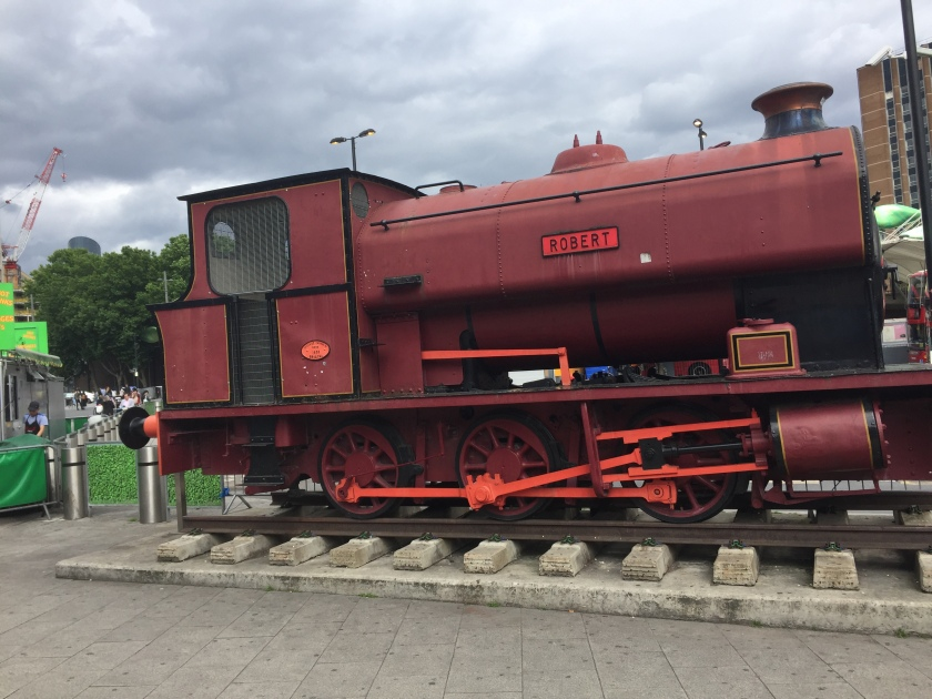 A large red steam train, with the name Robert in a small plaque on the side, on a small section of railway track placed outside Stratford Station.