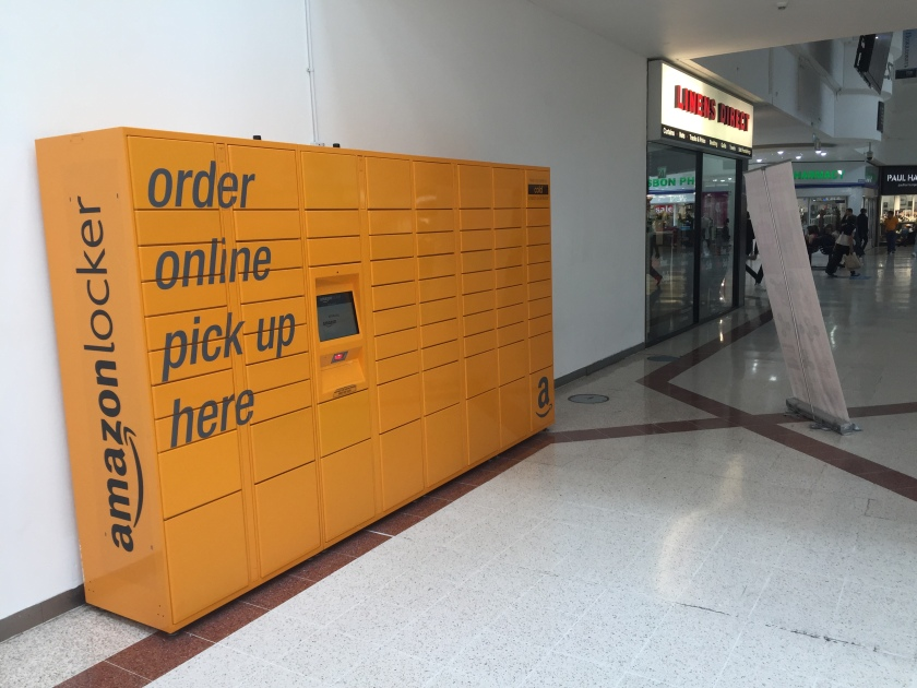 Next to the shop Linens Direct is a set of yellow lockers (8 by 10). Most rows are narrow in height, but rows 1 and 9 are a medium size, and the bottom row lockers are large. A touch screen sits in the middle rows of column 3 instead of lockers. Large text across columns 1 and 2 reads Order Online Pick Up Here. The words Amazon Locker are written vertically and prominently on the narrow left wall of the structure.