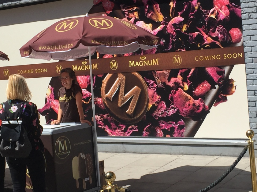 Sheltering from the sun under a Magnum themed umbrella, a lady at the Magnum stall serves a customer. Behind her, the shop wall is filled with an image of a fruity flavoured Magnum. A banner crosses the middle with the Magnum logo, and the words Coming Soon.