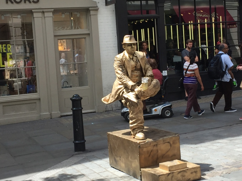 Completely covered in gold, a man dressed in a jacket, shirt, trousers and hat holds a beer while in a seated position in mid-air. His right foot is the only part of him in visible contact with the box below, as he's resting his left foot on his right knee.