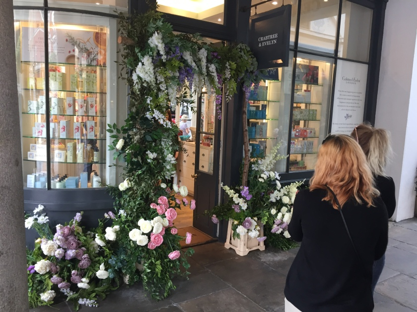The front of a shop called Crabtree & Evelyn. The door sits between two large windows. Below the windows and completely surrounding the doorway are lots of white, pink and blue flowers, and green leaves.