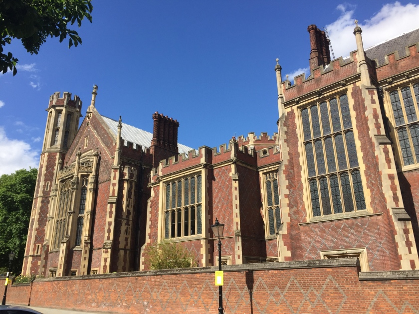 The large brick Lincoln's Inn building, looking a bit like a church. It has big windows along the structure, and criss-crossing grey diagonal lines forming diamond shapes on the brickwork.