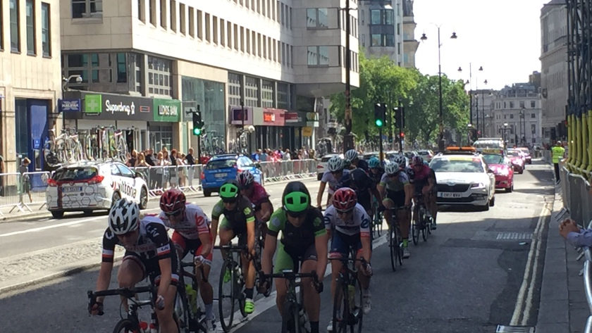 As part of the OVO Energy Women's Tour Stage 5, a group of cyclists race down the wide Strand road in London, with cars following behind. A small crowd is gathered behind the metal railings that stretch along the edge of the pavement.