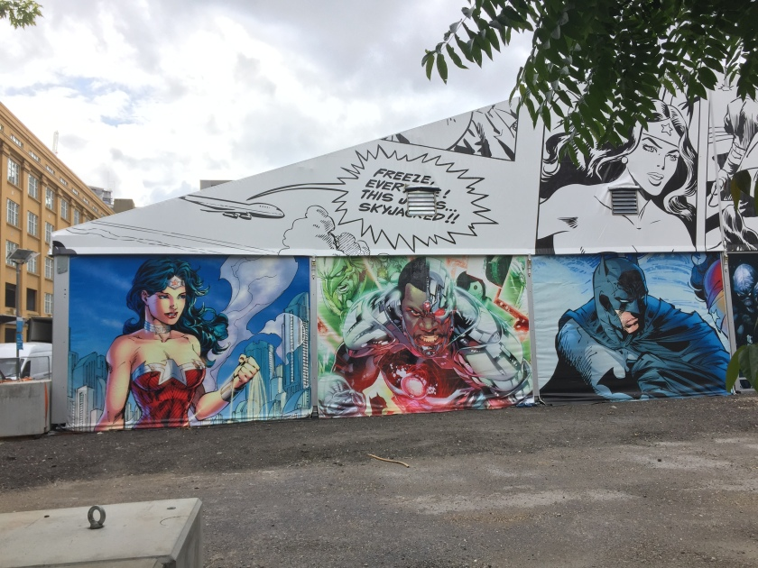"A mural in the form of a comic strip, stretching along the side of a single-floor building. Along the wall are colourful pictures of various superheroes, such as Batman. On the white roof above, a speech bubble comes out of a plane saying Freeze everyone! This jet is skyjacked!"", with black & white images of characters to its right."