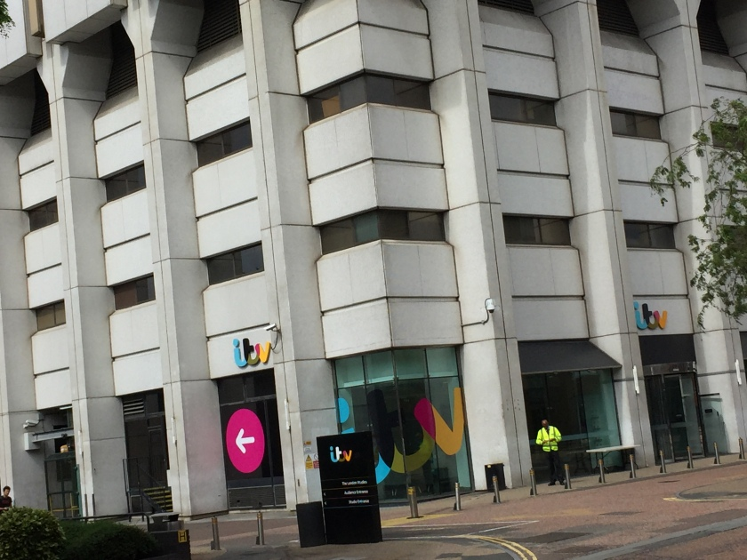 Bottom corner of the ITV studios tower, with the ITV logo splashed across the lowest corner window. A large pink circle with a white arrow points left on one of the lower left windows, while a tall black sign next to this points to the audience and studio entrances on the left of the building. A security guard is also standing outside in a hi-vis jacket.