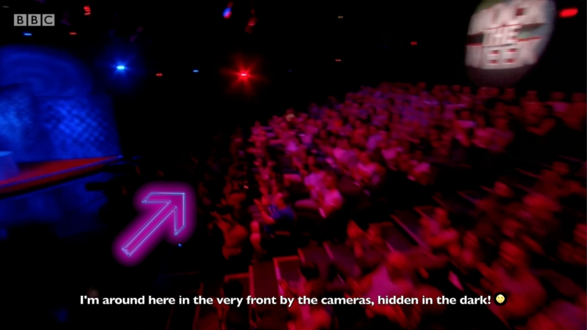 Screenshot of the audience from Mock The Week. An arrow points to the very front row, on the right of the central steps when facing away from them. The text reads - I'm around here in the very front by the cameras, hidden in the dark!