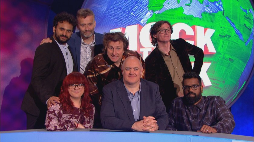 Group photo showing the guests gathered around Dara O Briain, in front of a large image of the Earth with Mock The Week in large text on top. On Dara's left is Angela Barnes, to his right is Romesh Ranganathan. Behind them, from left to right, are Nish Kumar, Hugh Dennis, Milton Jones and Ed Byrne.