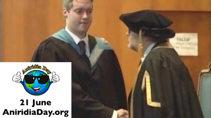 Photo of me at my university graduation ceremony. At bottom left is the Aniridia Day logo (a cartoon Earth wearing sunglasses and giving two thumbs up), the date (21 June) and the website (AniridiaDay.org).