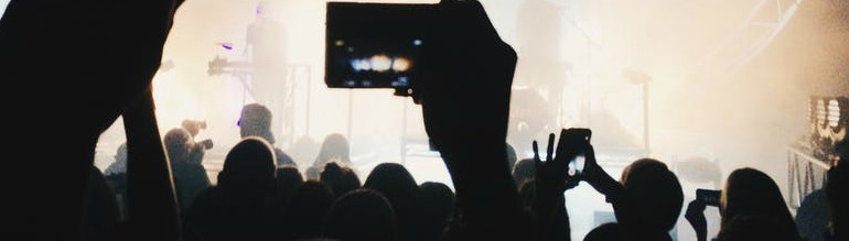 Audience members at a concert taking photos of the band performing on stage.