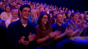Screenshot of the audience applauding on The Last Leg, including Glen on the right wearing a navy t-shirt with thin white and light-blue stripes.