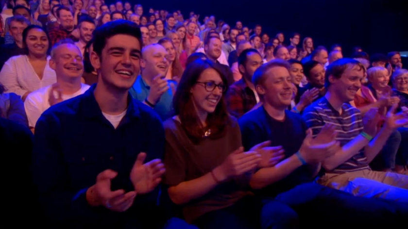 Screenshot of the audience applauding on The Last Leg, including me on the right wearing a navy t-shirt with thin white and light-blue stripes.
