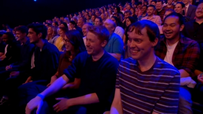 Screenshot of the audience laughing on The Last Leg, including Glen on the right wearing a navy t-shirt with thin white and light-blue stripes.