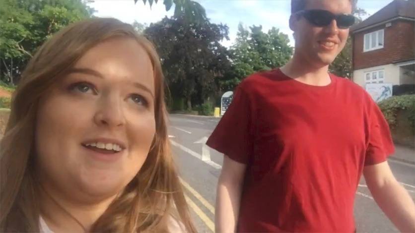 Emily and Glen smiling while walking along a street.