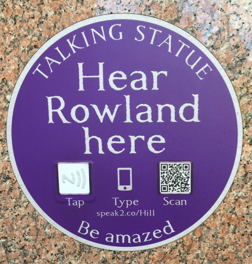 A round, blue plaque with the text Talking Statue, Hear Rowland Here, Be Amazed. Before the Be Amazed line, it has 3 options, allowing you to tap your phone against the plaque, type in a short web address, or scan a QR code.