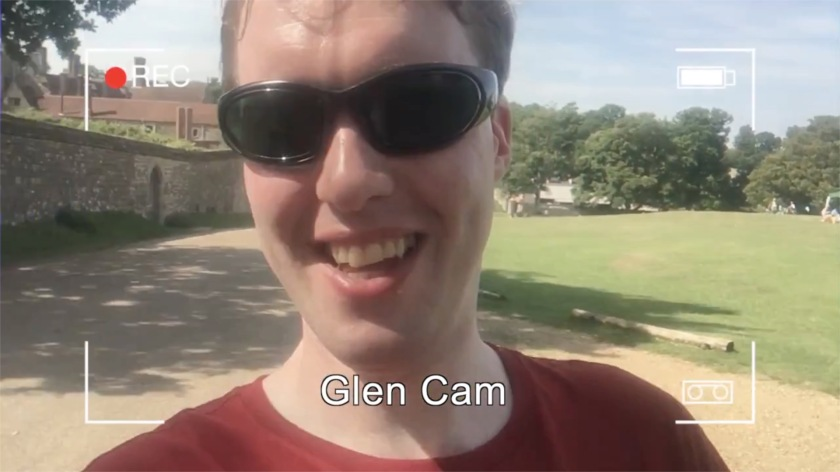 Glen wearing sunglasses and smiling at the camera in the sunshine. Overlaid on the image is a mockup of a camera recording screen, with 4 right-angled corner marks, a recording symbol top-left, a battery level indicator top-right, and the words Glen Cam centred at the bottom.