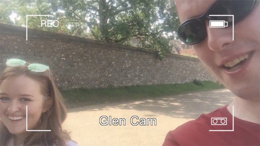 Emily and Glen smiling at the camera in the sunshine. Overlaid on the image is a mockup of a camera recording screen, with 4 right-angled corner marks, a recording symbol top-left, a battery level indicator top-right, and the words Glen Cam centred at the bottom.