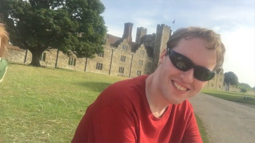 Glen sitting in the sunshine with the large Knole House in the background.