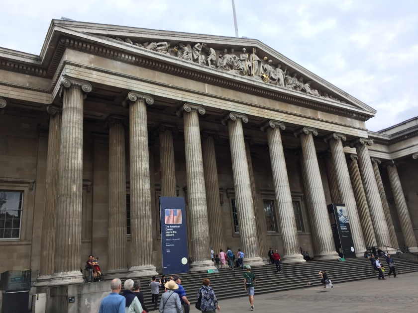 British Museum entrance. The top of the wide steps are 8 tall pillars, spaced along the width of the steps, above which is a triangular roof section containing various carved figures.