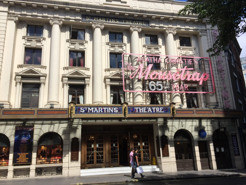 The outside of St Martin's Theatre. The theatre name is in white text on a blue background across the top of the doorway. Above this, hanging in front of the windows, is a large sign that says Agatha Christie's The Mousetrap, 65th Year. The play's title is in pink script lettering, the rest is in pink block capitals.