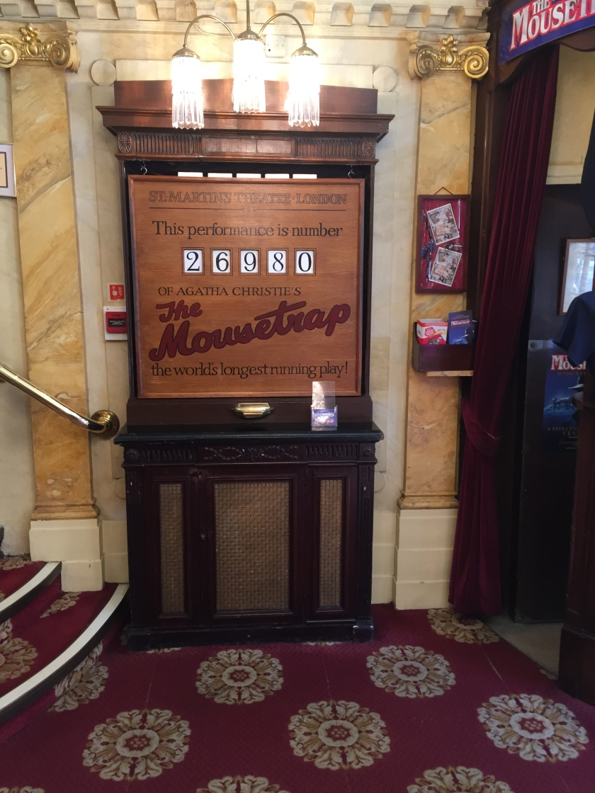 A large wooden sign that says - This performance is number 26980 of Agatha Christie's The Mousetrap, the world's longest running play. The black numbers are behind square holes, allowing them to change for each show.