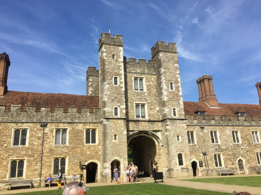 Knole House, a large stone building. In the centre are 2 towers with 5 floors, in between which is a wider tower with a large archway and 2 floors above it. Extending to each side, the lengthy extensions of the building are only 2 storeys high, with chimneys on top.