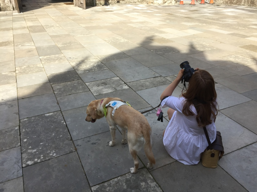 Emily kneeling on the paved floor in the shade, while pointing upwards with her camera, her guide dog Unity standing beside her.