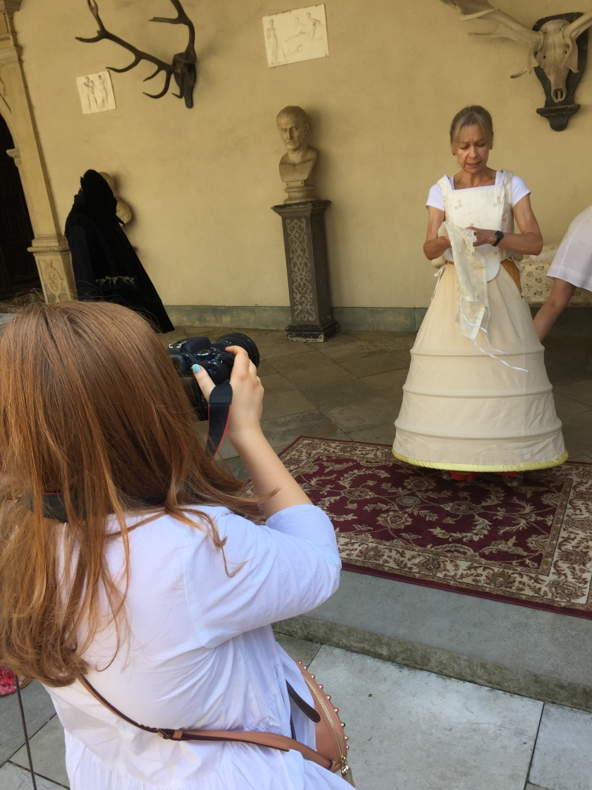 Emily taking a photo of a lady dressing up in the various layers of a Tudor outfit.