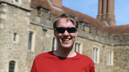 Glen smiling and wearing a red t-shirt and green tinted sunglasses, standing in front of the large Knole House building, which is blurred in the background.