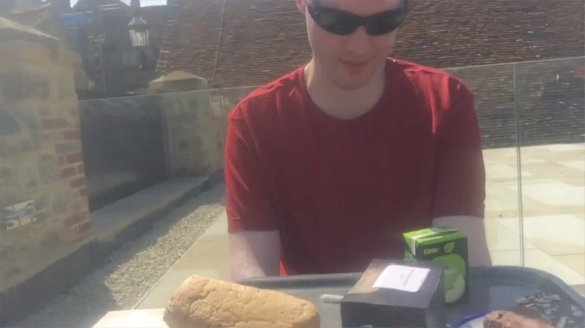 Me sitting at a table outside in the sunshine, with a tray of lunch in front of me, including a large roll, a sandwich, two cakes, and a carton of apple juice.